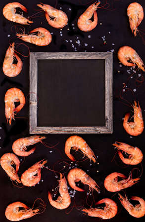Perfect cooked prawns shrimps with salt and text space chalk board top view flat lay layout food