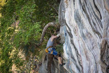 Young man rock climbing on a karst limestone white mountain in Thailand Stock Photo