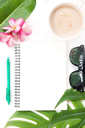 Tropical top view summer botanical concept still life sunglasses coffee cup notebook frame with plumeria frangipani leaves flower flat lay layout Stock Photo