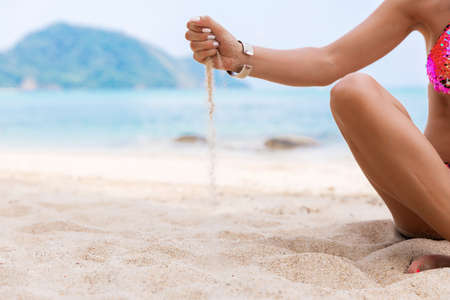 Woman on a white beach with sand in her hands at tropical exotic island Stock Photo