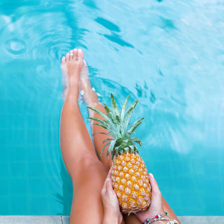 Slim woman holding pineapple fruit near swimming pool tropical exotic concept top view