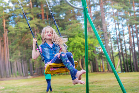 Pretty little blonde girl swinging outdoors on a playground