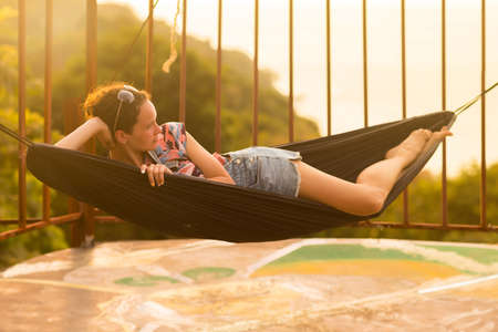 Young slim woman tropical exotic hammock in sunset lights