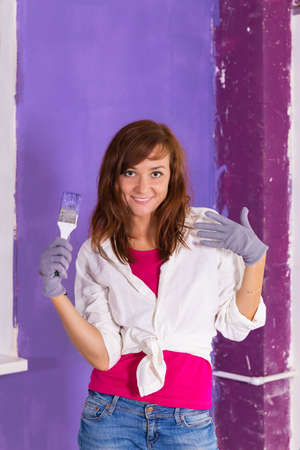 Young attractive woman paints white wall and purple paint brush