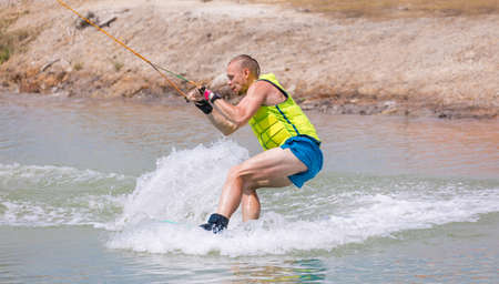 Man study wakeboarding on a blue lake summer sports