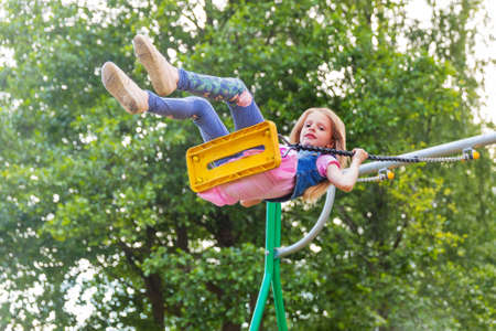 Pretty little blonde girl swinging outdoors on a playground Stock Photo