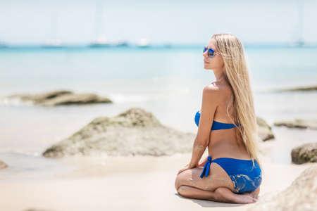Young pretty blond woman in blue bikini on a white tropic beach Stock Photo