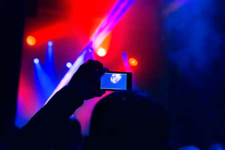Man taking  video by mobile phone of silhouettes crowd party concert music happy