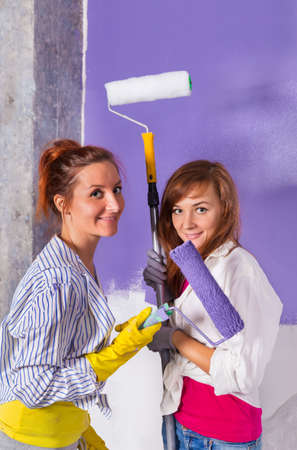 Young beautiful women paints white wall and purple paint roller