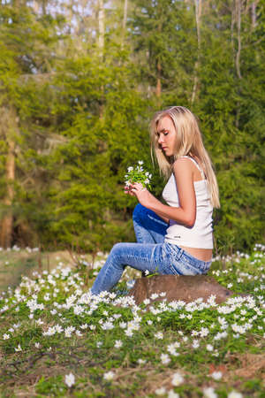 Pretty blonde woman on a spring meadow in blossom white flowers