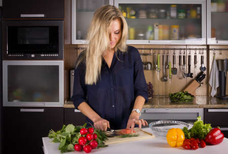 Young pretty blond young woman cooking salad in the kitchen