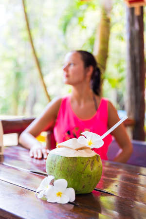 Fresh coconut drink with tropical palm leaves and white frangipani flowers in front of woman in tropical bar