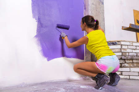 Young attractive woman paints white wall and purple paint roller Stock Photo