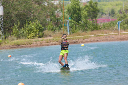 Woman study wakeboarding on a blue lake summer sports 版權商用圖片