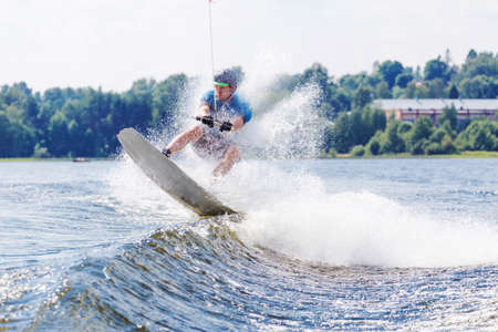 Young active man riding wakeboard on a wave from a motorboat on a summer lake