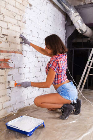 Young attractive woman paints white brick wall with paint brush Foto de archivo - 124747135