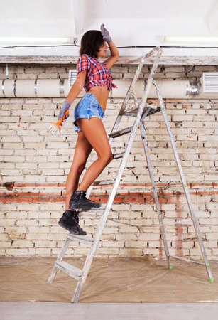 Young beautiful woman paints white brick wall and paint brush with ladder
