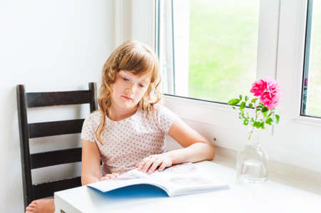 6 7 years: Interior portrait of a cute little girl reading a book
