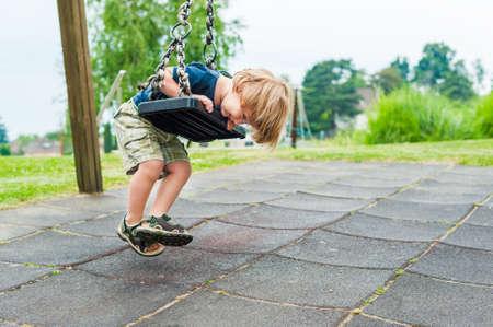 Cute peuter jongen spelen op speelplaats Stockfoto