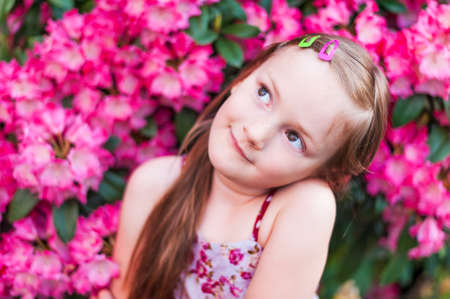 guessing: Cute little girl is daydreaming in pink flowers Stock Photo