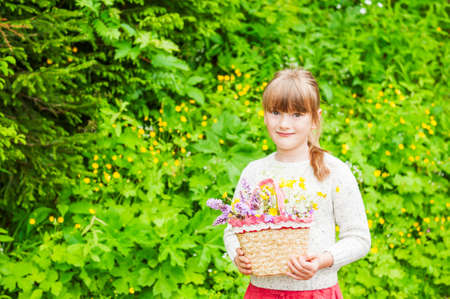 6 7 years: Portrait of a cute little girl with basket with flowers Stock Photo