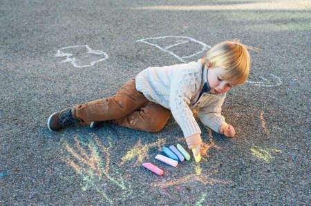 Schattige peuter jongen tekenen met krijt op een mooie dag in de buitenlucht