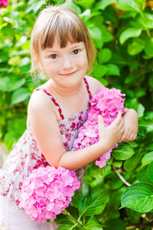 Summer portrait of a cute little girl with hydrangea photo