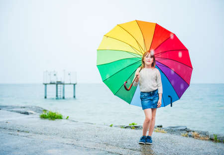Outdoor portrait of a cute little girl with colorful umbrella under the rain photo