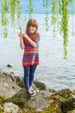 colegiala: Retrato al aire libre de una ni�a linda en un buen d�a soleado, jugando junto al hermoso lago