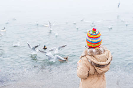 cold day: Cute little girl feeding birds on a cold day