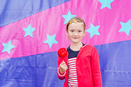 pomme: Beautiful little girl in amusement park with pomme damour Stock Photo