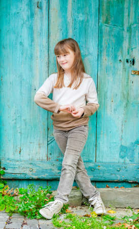 seven persons: Outdoor portrait of a cute little girl, standing next to turquoise door, wearing beige pullover, pants and shoes