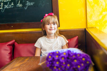 neckless: Portrait of a pretty little girl with pearl neckless in a cafe