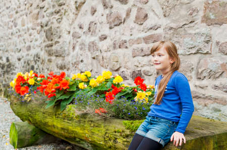 lifestile: Outdoor portrait of a cute little girl sitting next to flowers Stock Photo