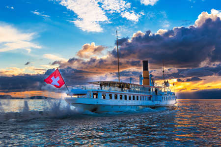 Ancien bateau à vapeur avec le drapeau suisse flottant sur le lac de Genève sur le coucher du soleil