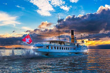 Ancien stoomboot met Zwitserse vlag drijvend op het meer van Genève op zonsondergang