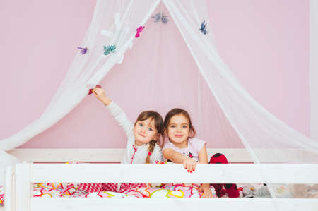 Adorable little girls playing together on the bed photo