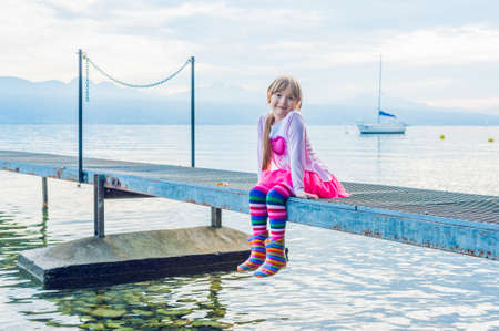 skirts: Cute little girl sitting on a pier, wearing, colorful tights and boots, pink skirt tutu and top with a heart Stock Photo