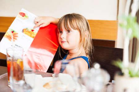 Schattige kleine Giel kiezen van haar maaltijd in het menu van een kind in een restaurant Stockfoto