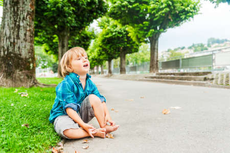 sitting on the ground: Outdoor portrait of a cute toddler boy Stock Photo