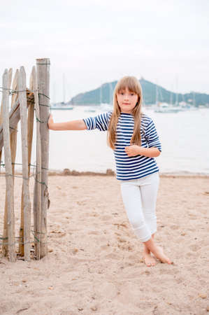 frock: Cute little girl standing on a sand beach, wearing a frock and white jeans
