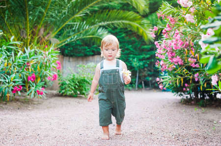 Adorable toddler boy walking with flowers in his hand Archivio Fotografico