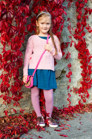 skirts: Pretty girl posing outdoor, wearing blue dress and pink pullover, shiny tennis shoes, red ivy and stone wall on background Stock Photo