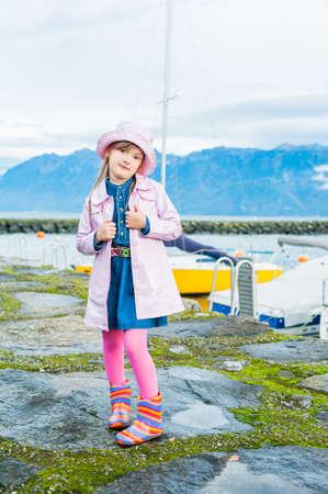 rain boots: Retrato al aire libre de una ni�a linda, vestido con chaqueta de color rosa lluvia de vinilo y un sombrero, botas de lluvia de colores y medias de color rosa