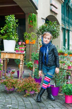 Portrait of a cute little girl in a city