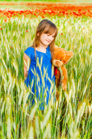Summer portrait of a cute little girl playing with teddy bear in a wheat field photo