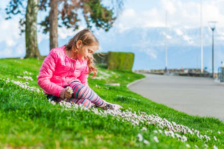 Beautiful little girl playing with flowers in a park on a nice sunny day in a early spring, wearing bright pink jacket photo