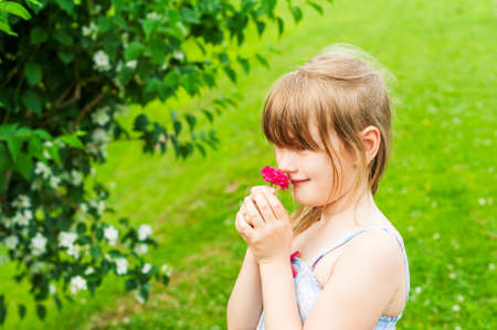 6 7 years: Little girl smelling a pink rose Stock Photo