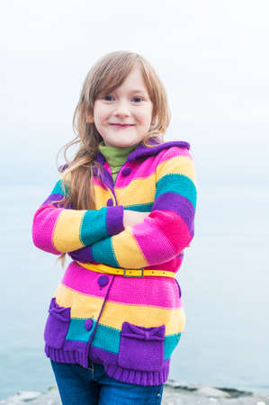 Outdoor portrait of a beautiful little girl in colorful jacket photo