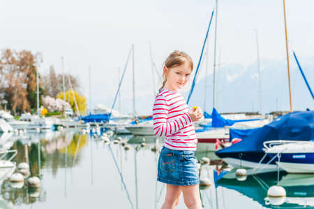 jeans skirt: Cute little girl resting next to lake, weraing red and white top and jeans skirt